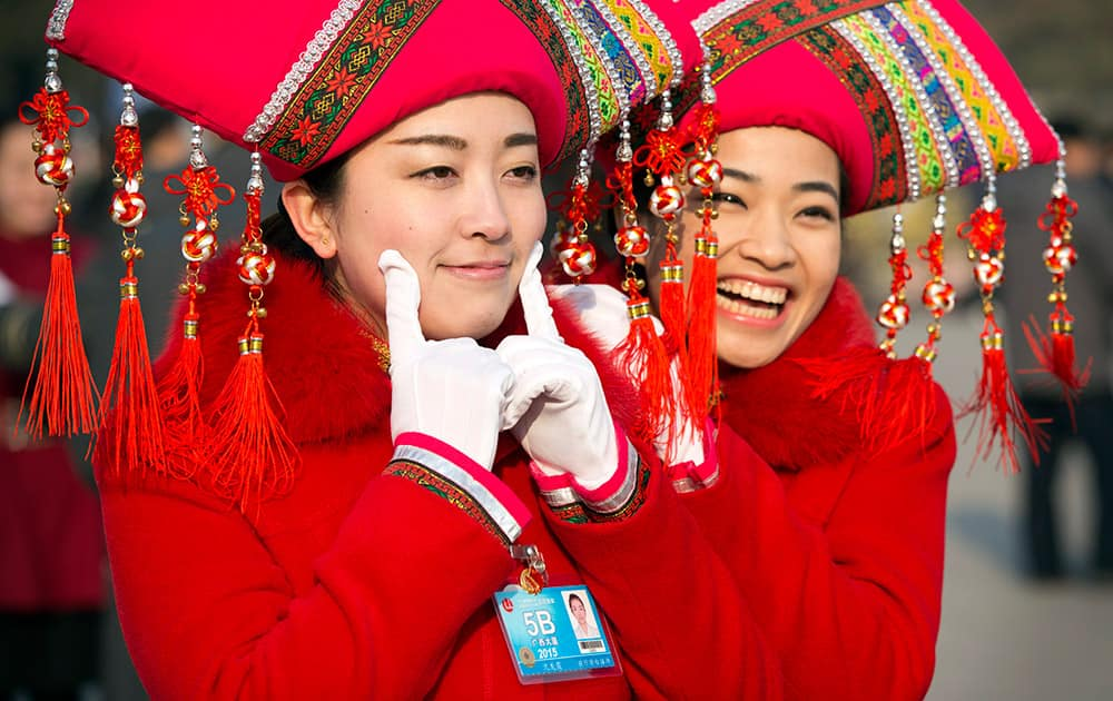 Hostesses pose for photos outside the Great Hall of the People during the opening session of the annual National People's Congress in Beijing.
