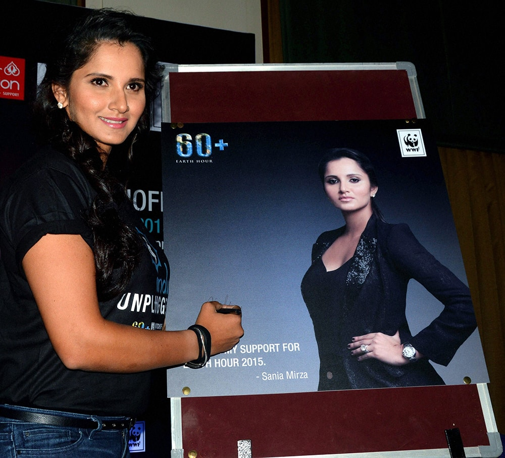 Tennis star and ambassador of Earth Hour 2015, Sania Mirza signs a poster during a press conference organized by WWF in Hyderabad.