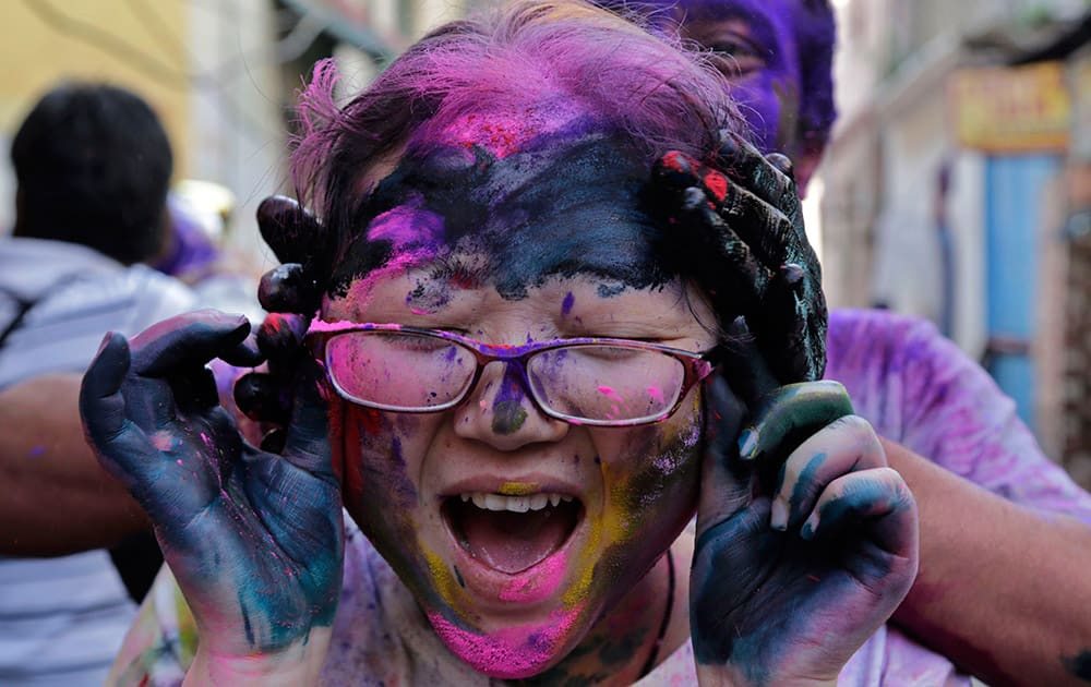 A foreign tourist screams as another puts color on her face during celebrations marking Holi in Kolkata.
