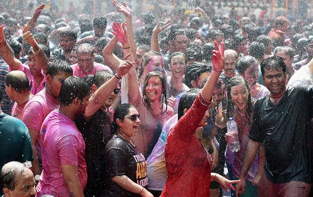 Foreigners along with locals celebrate Holi festival in Mumbai.