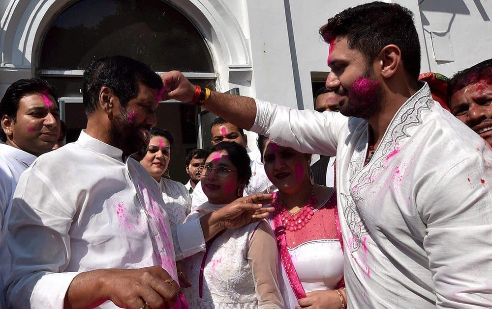 Lok Janshakti Party president Ram Vilas Paswan with his wife and son Chirag Paswan celebrating Holi at his residence in New Delhi.
