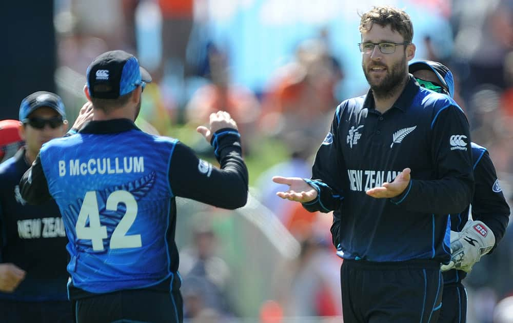 New Zealand bowler Dan Vettori, right, is congratulated by his captain Brendon McCullum after he bowled Afghanistan batsman Usman Ghani for no score during their Cricket World Cup Pool A match in Napier, New Zealand.
