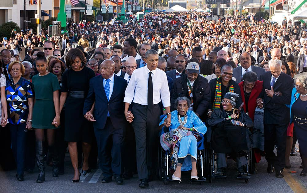 President Barack Obama, center, walks as he holds hands with Amelia Boynton Robinson, who was beaten during