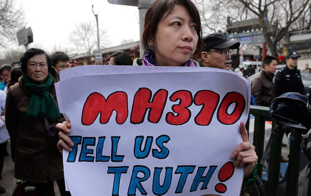 A relative of passenger on board the Malaysia Airlines Flight 370 that went missing on March 8, 2014, holds a placard as she walks with other family members of the missing passengers after a gathering at Yonghegong Lama Temple in Beijing.