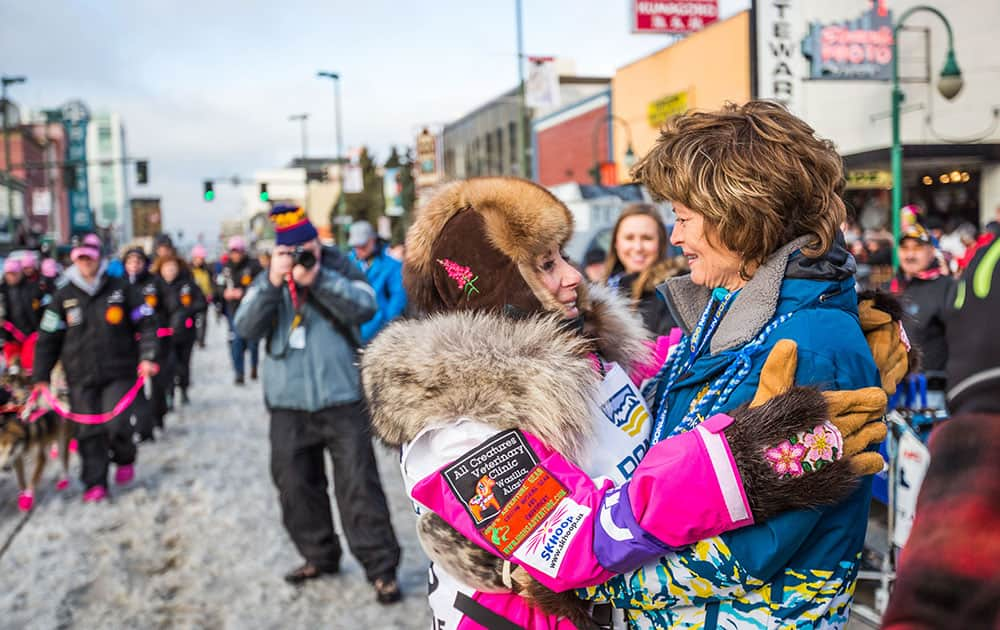 Musher DeeDee Jonrowe, left, gets a hug from Sen. Lisa Murkowski before the ceremonial start of the Iditarod Trail Sled Dog Race, in Anchorage, Alaska.