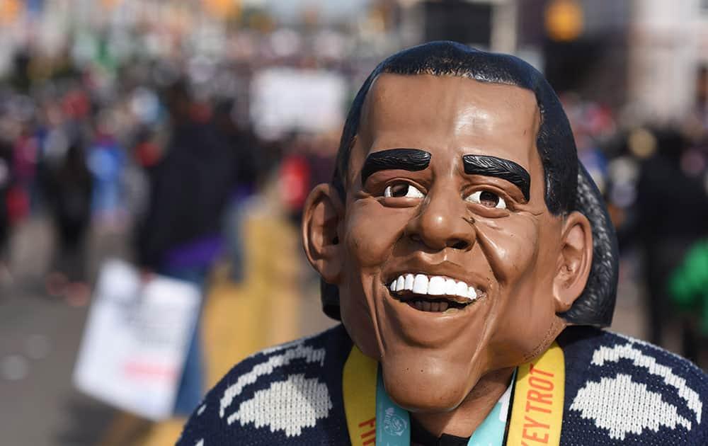 R Jesus McNair of Detroit, walks on the Edmund Pettus Bridge with his President Barack Obama mask, in Selma, Ala.