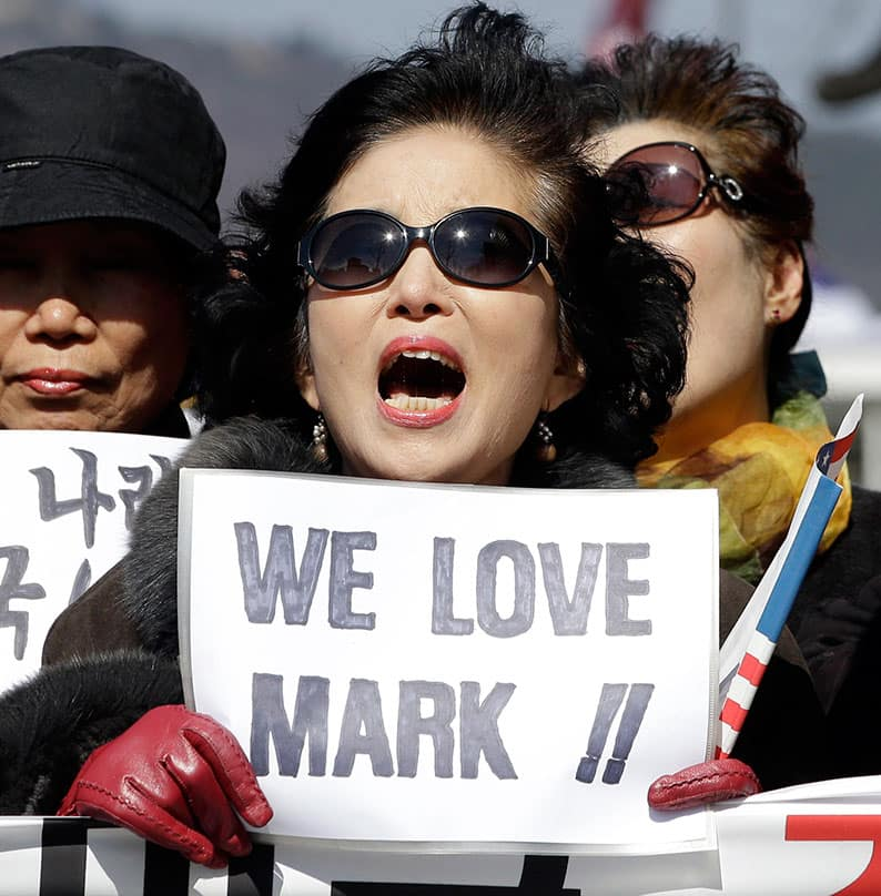 A woman holds a sign during a rally denouncing the attack on U.S. Ambassador to South Korea Mark Lippert in downtown Seoul, South Korea.