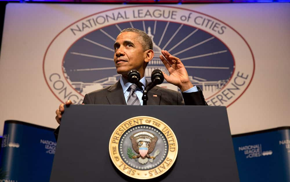 President Barack Obama gestures that he is listening to the crowd as he speaks at the National League of Cities annual Congressional City Conference in Washington.