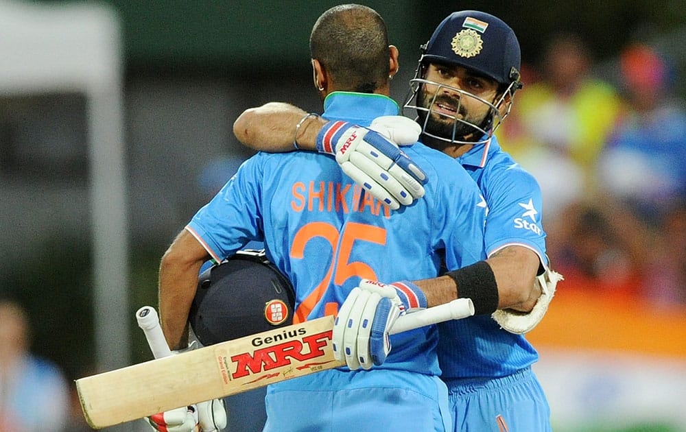 India's Virat Kohli, right, congratulates teammate Shikhar Dhawan after scoring a century while batting against Ireland during their Cricket World Cup Pool B match in Hamilton, New Zealand.