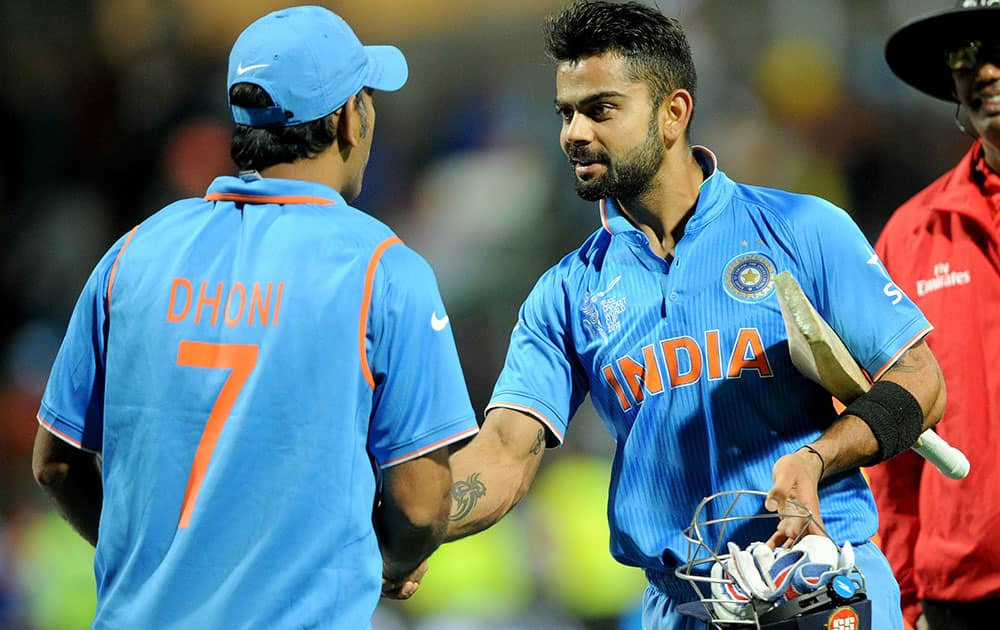 India's Virat Kohli, right, is congratulated by his captain MS Dhoni after they defeated Ireland by eight wickets in their Cricket World Cup Pool B match in Hamilton, New Zealand.