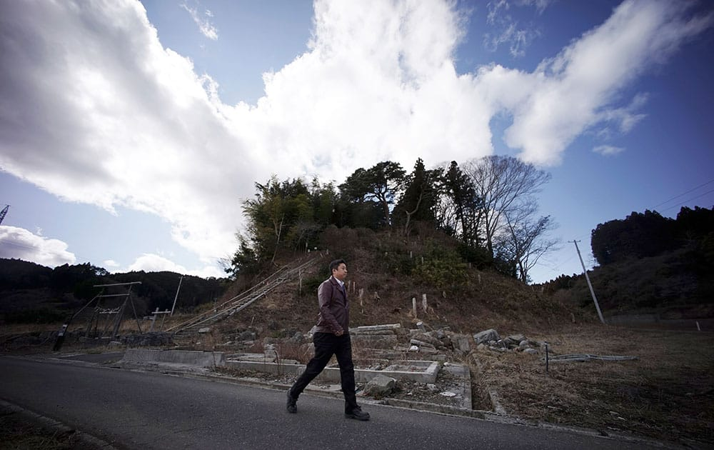 Michihiro Kono, president of Yagisawa Syoten Co., walks by a hill where his company's employees ran up to a shrine for safety when the 2011 tsunami hit Rikuzentakata, Iwate Prefecture, northeastern Japan.