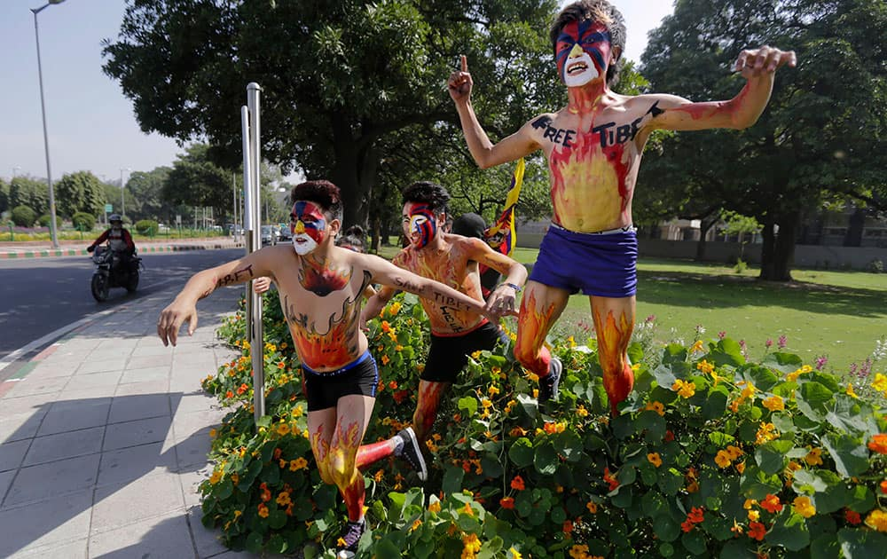 Tibetan exiles, their faces painted in the colors of the Tibetan flag, jump over a flower bed as they make their way towards the Chinese Embassy during a protest in New Delhi, India.