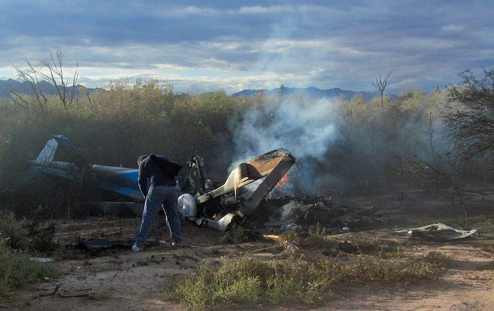 A man stands next to the wreckage of one of two helicopters that apparently collided in midair, near Villa Castelli, in Argentina's La Rioja province.