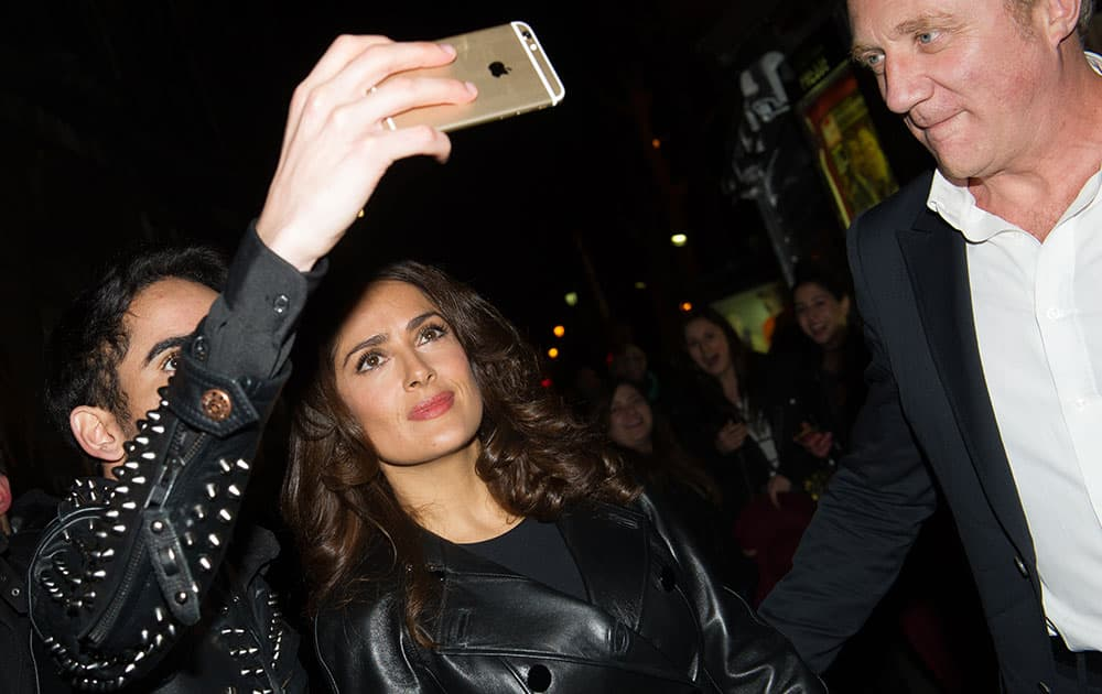 Mexican actress Salma Hayek has a photo taken with a fan as she leaves Alexander McQueen's ready-to-wear fall-winter 2015-2016 fashion collection presented during Paris fashion week.