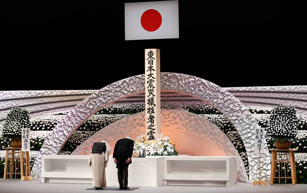 Japan's Emperor Akihito and Empress Michiko bow in front of the altar for the victims of the March 11, 2011 earthquake and tsunami, at the national memorial service in Tokyo.