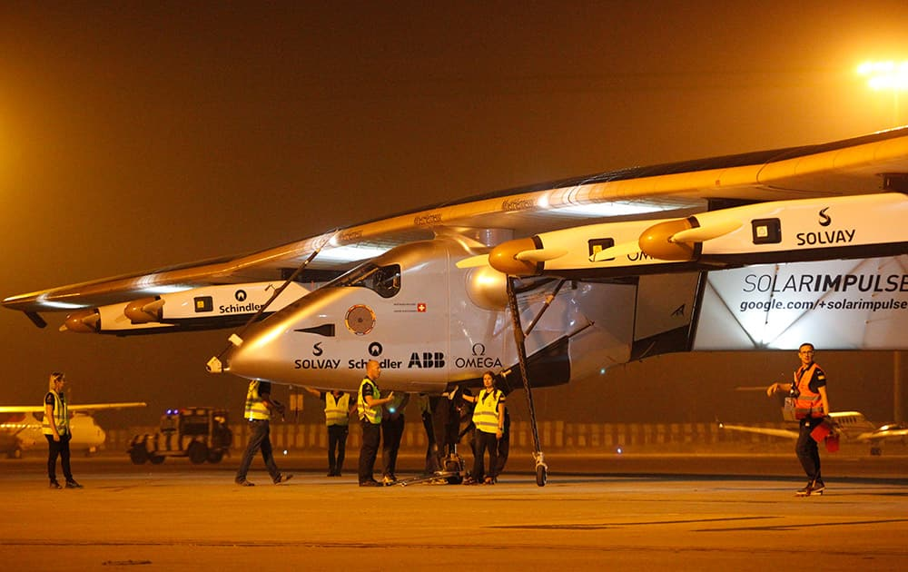 Crew members gather to push the Solar Impulse 2 towards a hangar after it landed at an airport in Ahmadabad. The Swiss-made solar powered aircraft landed in western India on Tuesday night, completing the second leg, and its first sea crossing, of its historic round-the-world trip.