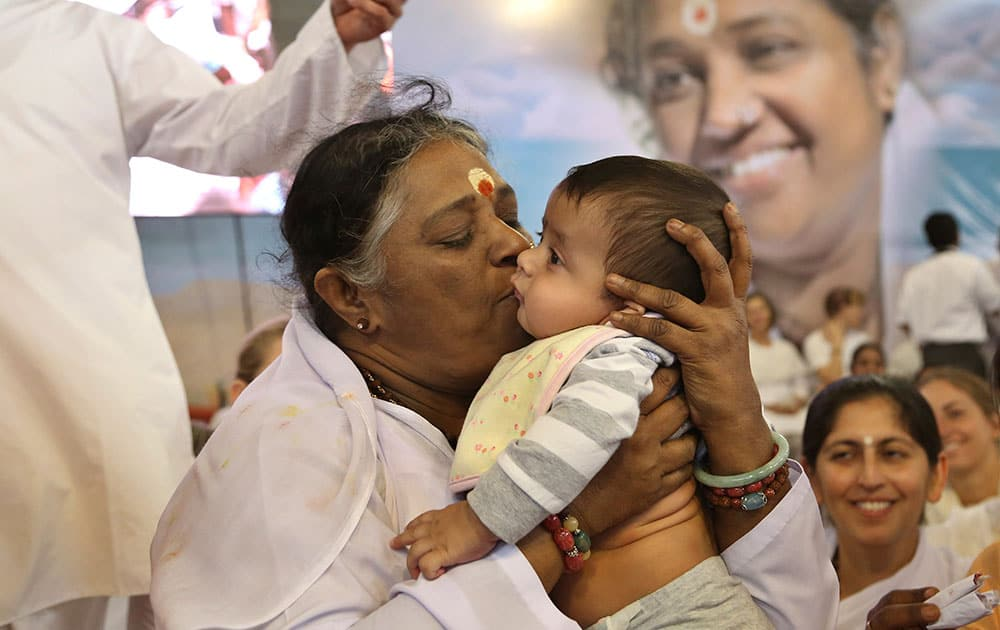 Indian spiritual leader Mata Amritanandamayi kisses to bless a child of a devotee during a prayer meeting in Bangalore.