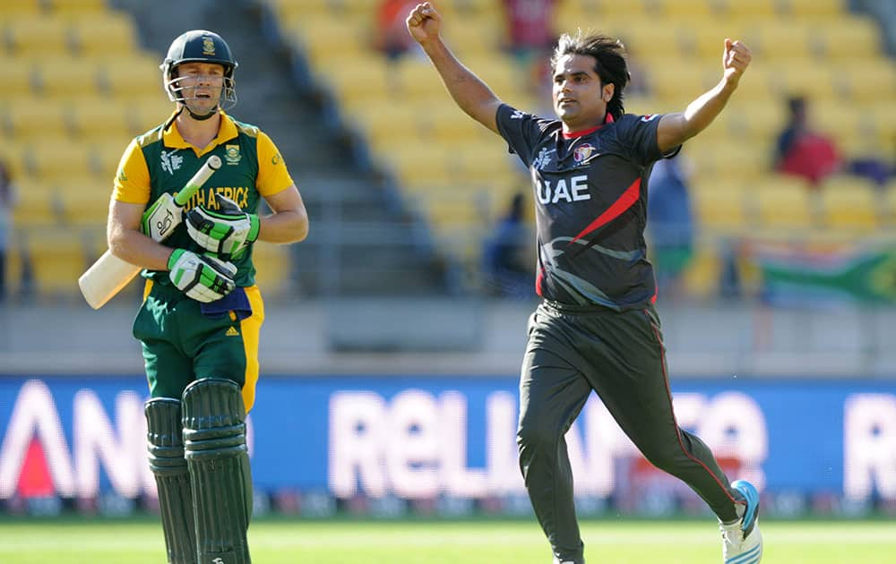 South African batsman A.B de Villiers, left, walks as United Arab Emirates bowler Kamran Shahzad celebrates after he was out caught for 99 runs during their Cricket World Cup Pool B match in Wellington, New Zealand.