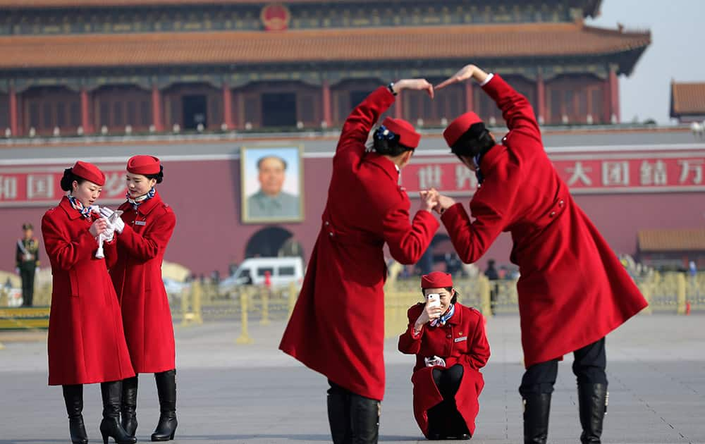 Chinese hostesses, who serve the delegates of the National People's Congress, have souvenir photos taken on Tiananmen Square during a plenary session of the NPC held at the Great Hall of the People in Beijing.
