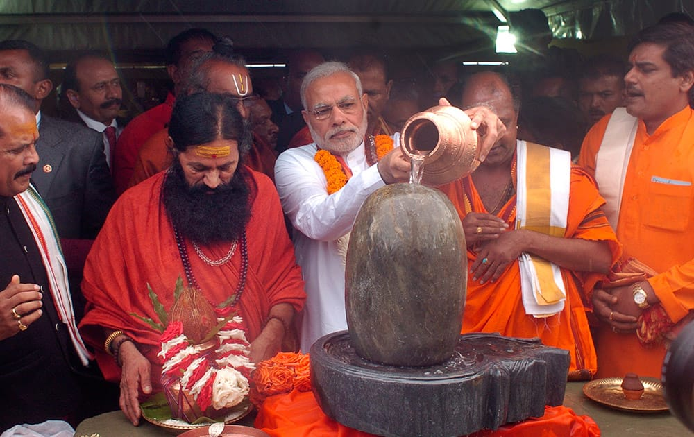 Prime Minister Narendra Modi, pours holy water on a lingam or shivling, a representation of the Hindu deity Shiva used for worship, during a Hindu religious ceremony at the crater lake of Grand Bassin (also known as Ganga Talao), during the second day of his visit to the Republic of Mauritius.