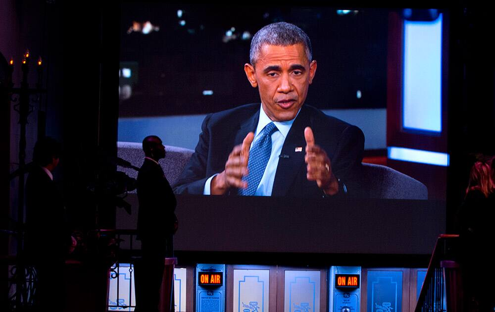 A Secret Service Agent stands by a screen showing a live feed as President Barack Obama talks with Jimmy Kimmel while they are taped on Jimmy Kimmel Live, in Los Angeles.