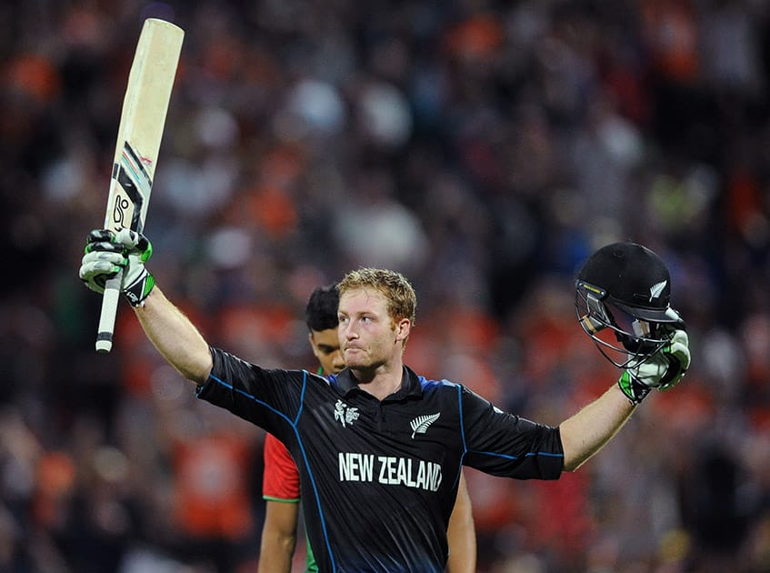 New Zealand's Martin Guptill waves his bat as he celebrates after scoring a century while batting against Bangladesh during their Cricket World Cup Pool A match in Hamilton, New Zealand.