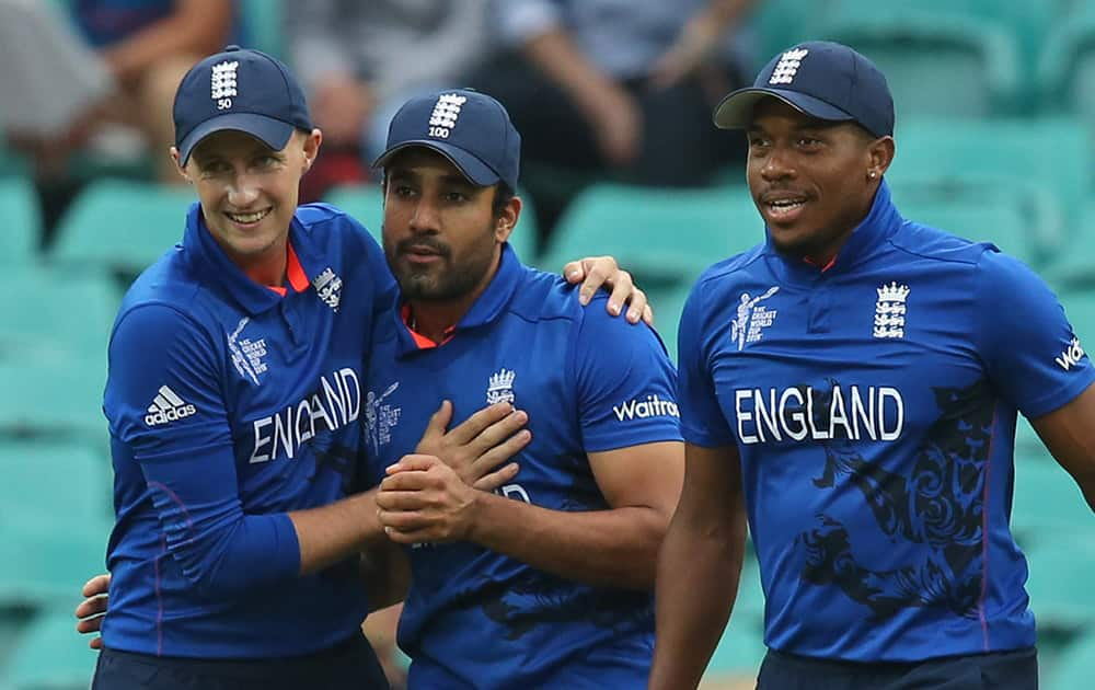 England's Chris Jordan, right, and Joe Root congratulate teammate Ravi Bopara, center, for the dismissal of Afghanistan's Shafiqullah during their Cricket World Cup pool A match in Sydney.
