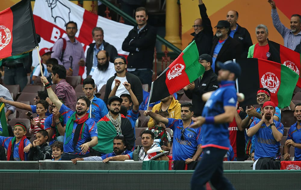 Afghanistan fans wave their national flags and cheer for their team, as an English cricketer fields during their Cricket World Cup pool A match in Sydney.