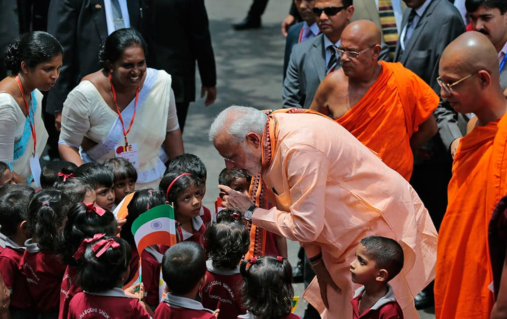Prime Minister Narendra Modi interacts with school children during his visit to the Maha Bodhi Buddhist temple in Colombo, Sri Lanka.