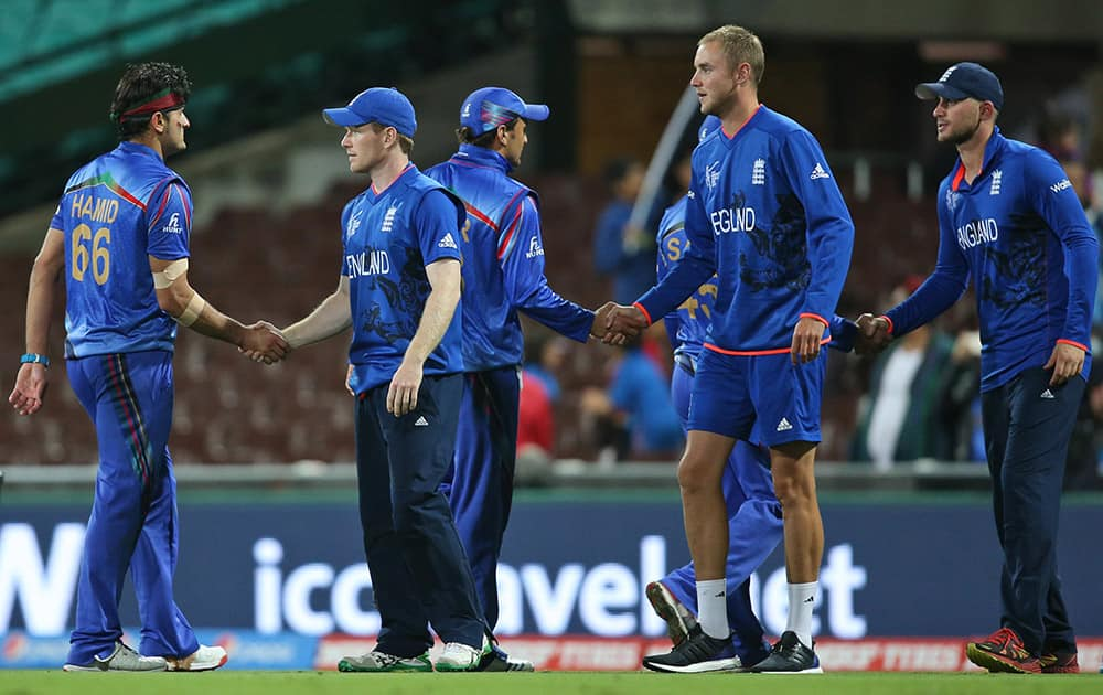 Afghanistan's Hassan Hamid shakes hand with England's captain Eoin Morgan, during their Cricket World Cup pool A match in Sydney, Australia.