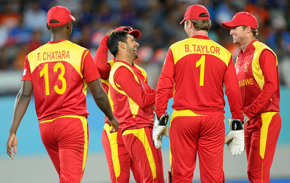 Zimbabwe's Raza Butt, is congratulated by his teammates after dismissing India's Virat Kohli during their Cricket World Cup Pool B match in Auckland.