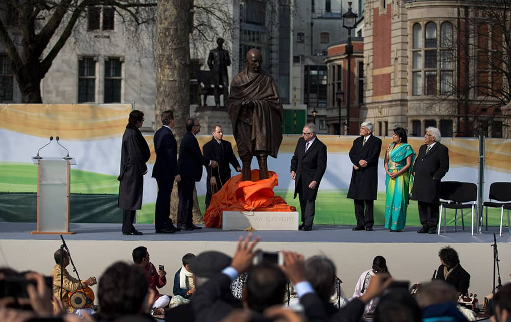 A new statue of Mahatma Gandhi by British sculptor Philip Jackson is unveiled by Finance Minister Arun Jaitley, watched by Amitabh Bachchan, British Prime Minister David Cameron and Gandhi's grandson Gopalkrishna Gandhi, third right, in Parliament Square, London.