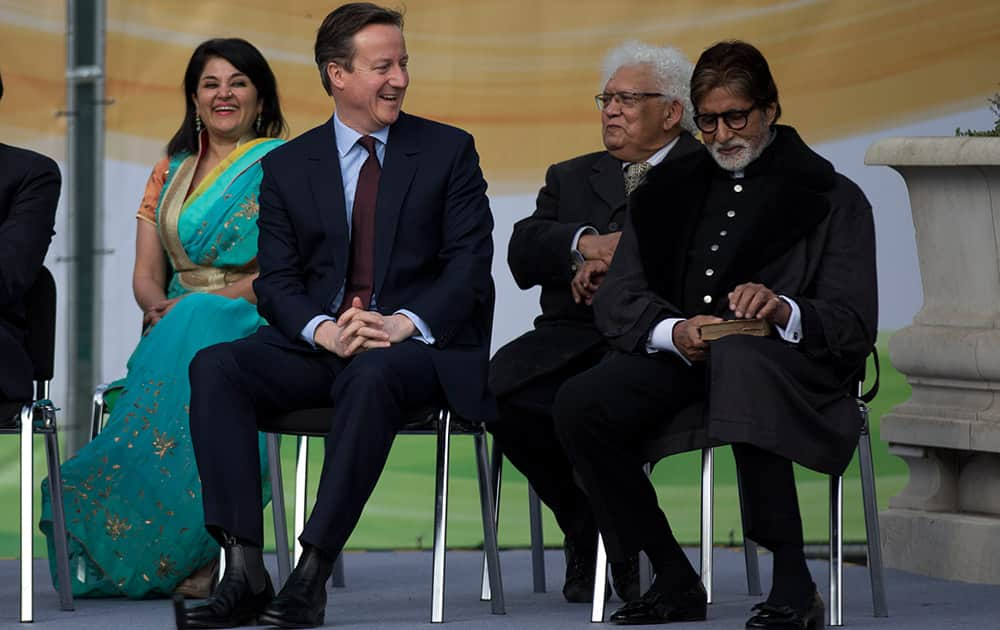 British Prime Minister David Cameron sits on the stage next to Bollywood actor Amitabh Bachchan during the unveiling ceremony for a new statue of Mahatma Gandhi by British sculptor Philip Jackson in Parliament Square, London.