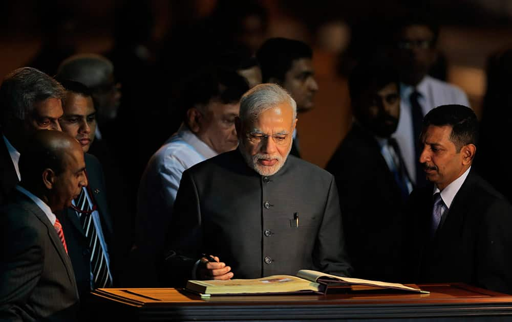 Prime Minister Narendra Modi signs the visitor's book upon his arrival in Colombo, Sri Lanka.