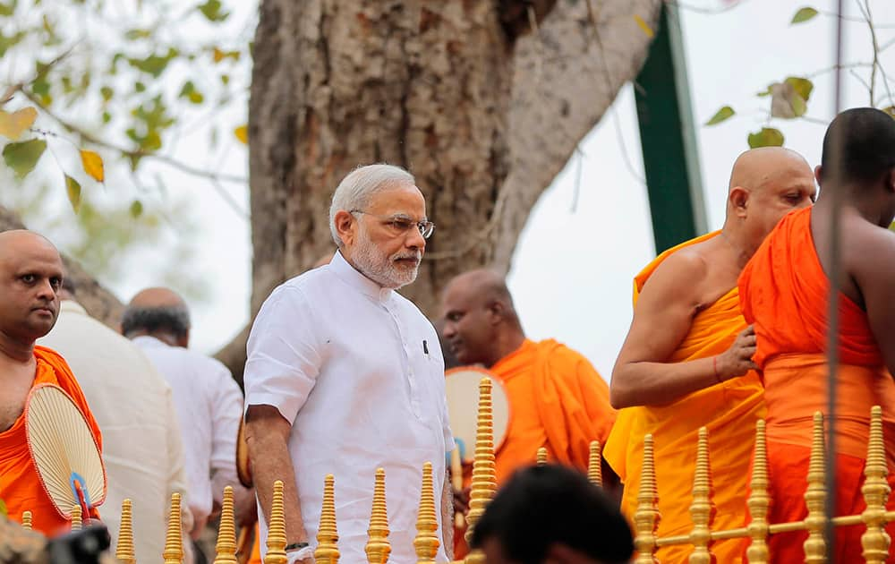 Prime Minister Narendra Modi walks after paying homage to Sri Maha Bodhi, the sacred Bo tree said to have been propagated from the tree under which Buddha is believed to have achieved enlightenment, in Anuradhapura about 230 kilometers north east of Colombo, Sri Lanka.