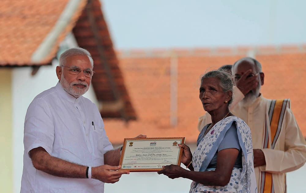 Prime Minister Narendra Modi hands over a certificate to a Sri Lankan woman, marking the completion of her home under a housing scheme funded by the Indian government for war victims in Llavalai, northwest of Jaffna, Sri Lanka.