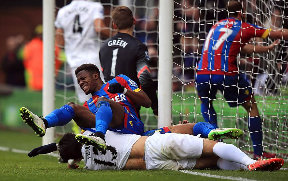 Crystal Palace's Wilfried Zaha collides with the post after scoring against Queens Park Rangers during the English Premier League soccer match at Selhurst Park, London.