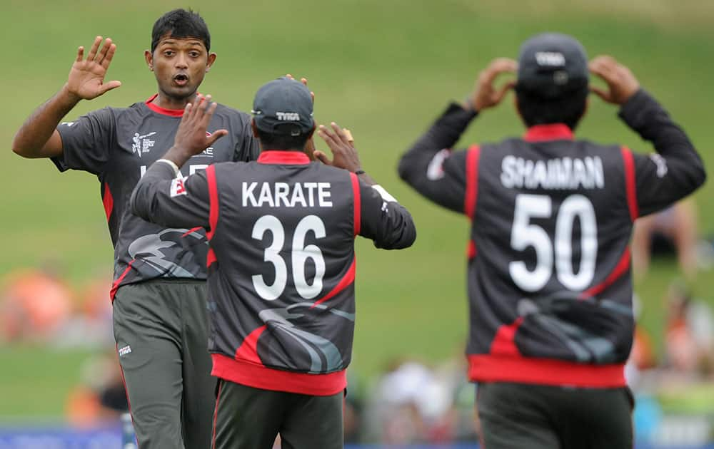 United Arab Emirates bowler Amjad Javed, left, celebrates with teammates K. Karate and Shaiman Anwar, right, after taking the wicket of West Indies batsman Johnson Charles during their Cricket World Cup Pool B match in Napier, New Zealand.