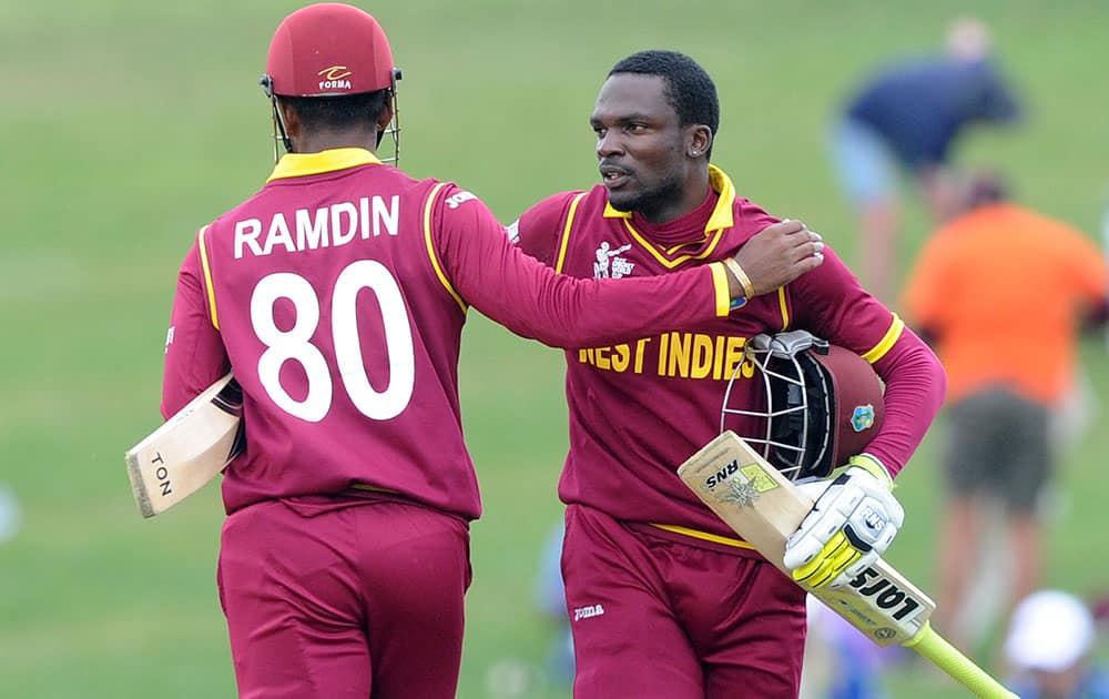 West Indies batsman Denesh Ramdin, left, celebrates with teammate Jonathan Carter after they won their Cricket World Cup Pool B match by six wickets against the United Arab Emirates in Napier, New Zealand.