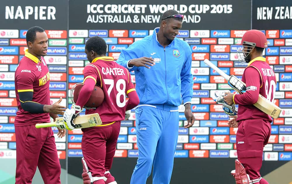 West Indies batsmen Denesh Ramdin, right, is congratulated by his captain Jason Holder as Jonathan Carter is congratulated by Dwayne Smith, left, after they won their Cricket World Cup Pool B match by six wickets against the United Arab Emirates in Napier, New Zealand.