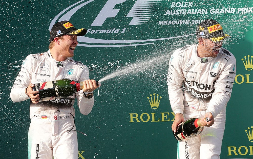 Mercedes driver Nico Rosberg, left, of Germany sprays champagne on teammate Lewis Hamilton of Britain on the podium after the Australian Formula One Grand Prix at Albert Park in Melbourne, Australia.