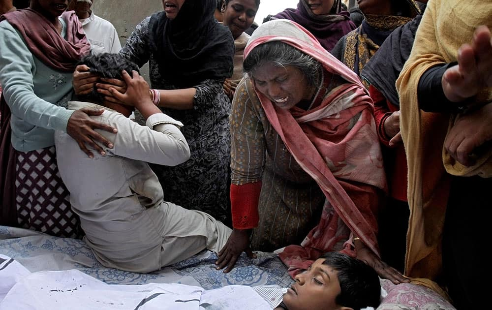 A Pakistani Christian family mourn next to the lifeless body of a boy who was killed from a suicide bombing attack near two churches in Lahore, Pakistan.