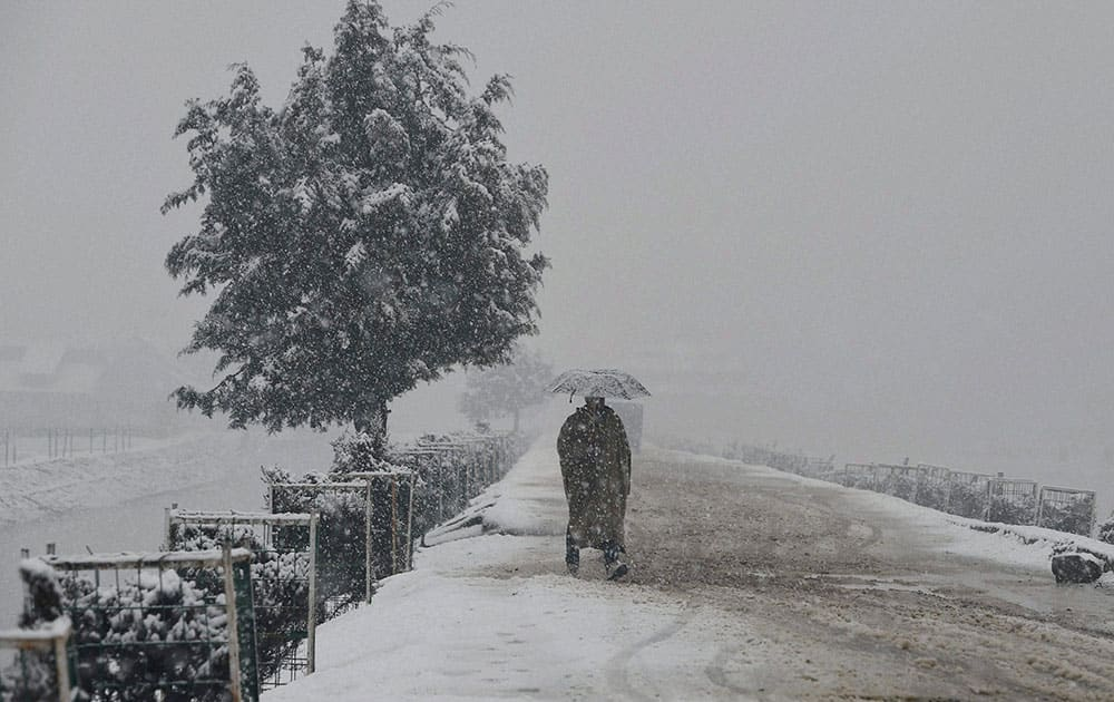 A man walks with umberalla during heavy snowfall in Srinagar.