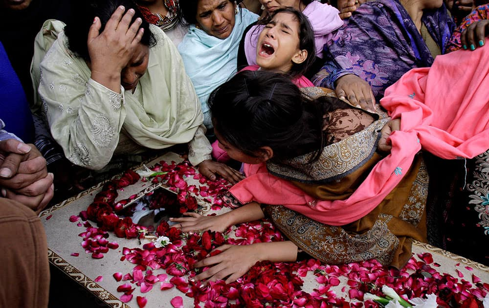 Family members of Pakistani Christian community mourn the death of a victim of Sunday's suicide bombings that struck two churches, in Lahore, Pakistan.