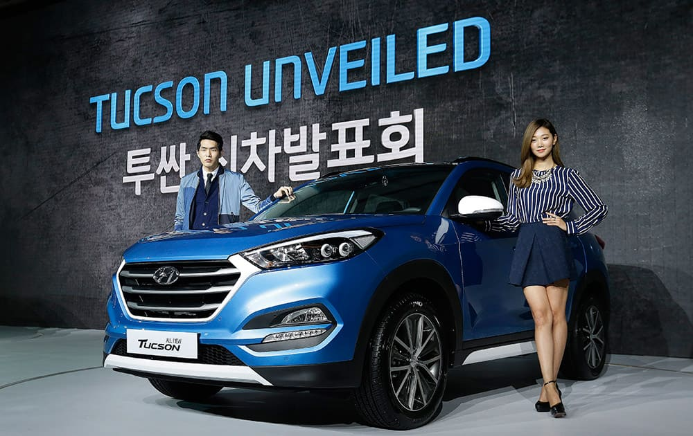 South Korean models pose with Hyundai Motors' all-new Tucson SUV during a press unveiling in Seoul, South Korea. The vehicle, equipped with a U2 1.7 diesel engine or R2.0 diesel engine, are priced from 23.4 million won (US$20,763) to 29.2 million won (US$25,909) .