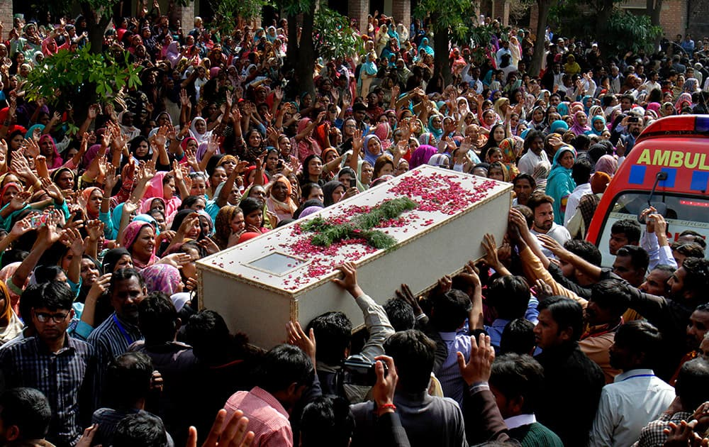 Pakistani Christians carry a casket of a victim of Sunday's pair of suicide attacks on two churches during a mass funeral service in Lahore.