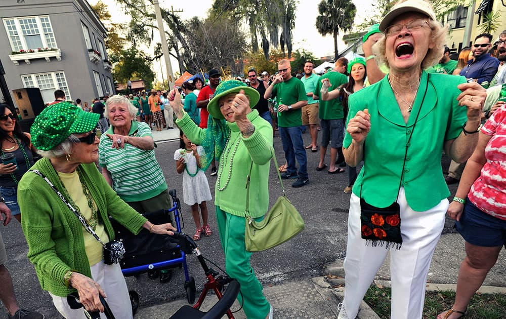A group of ladies from the Riverside Presbyterian Apartments from left, Virginia Happel, Jackie Ogilvie, Di Tyree and Joyce Hallmark, stop to dance as O'Brothers Irish Pub celebrates St. Patrick's Day with a street party in Jacksonville, Fla.