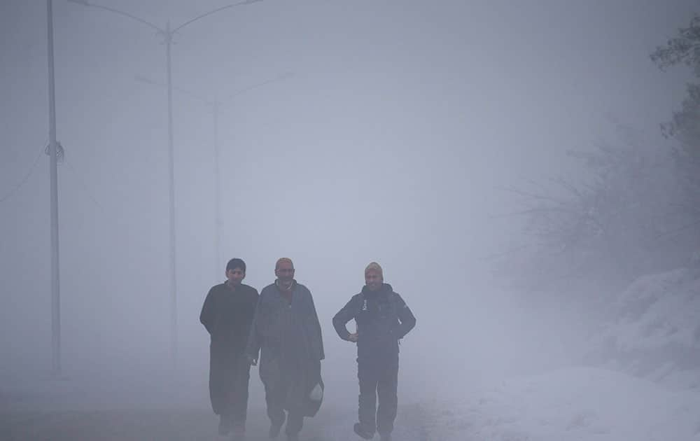 Kashmiri villagers walk on a road engulfed in fog in Tangmarg, about 38 kilometers (24 miles) northwest of Srinagar, India.