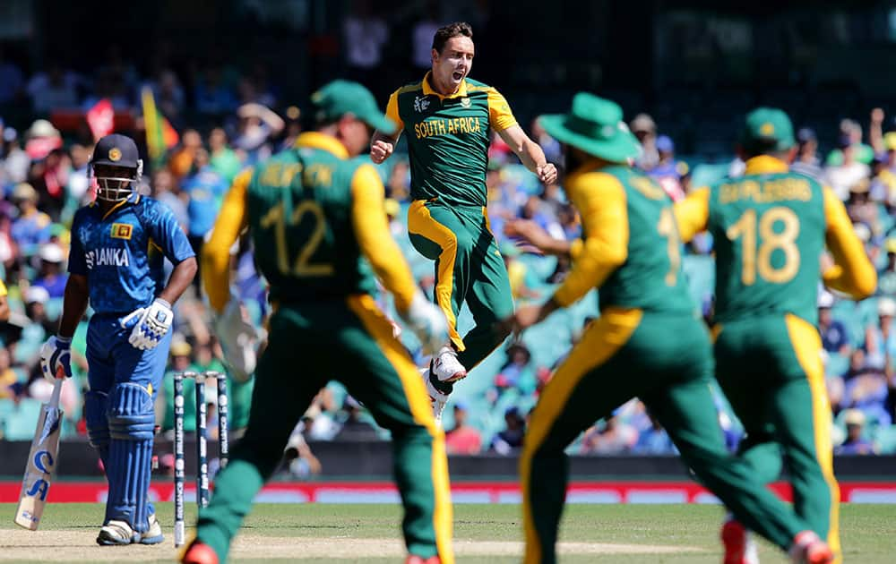 South Africa's Kyle Abbott leaps in the air as he celebrates the dismissal of Sri Lanka's Kusal Perera, left, during their Cricket World Cup quarterfinal match in Sydney, Australia.