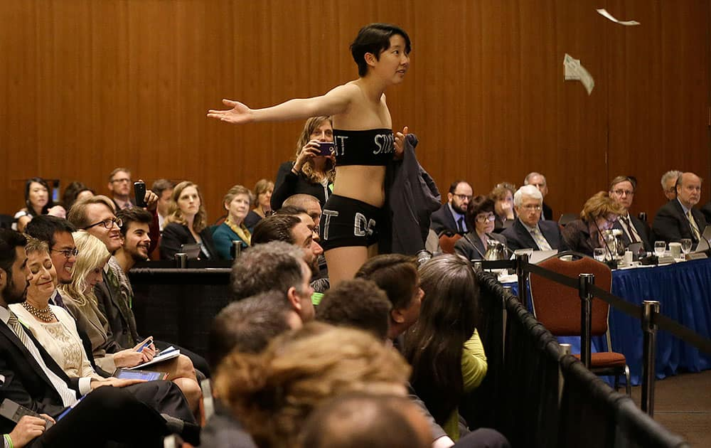University of California Berkeley student Kristian Kim throws fake money while starting a protest during a UC Board of Regents meeting in San Francisco.
